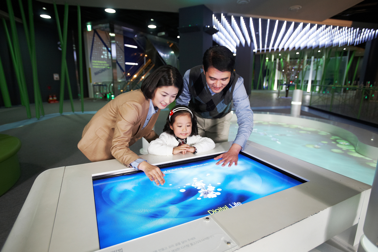 Touched the large screen of the touch screen family (father, mother, girl)