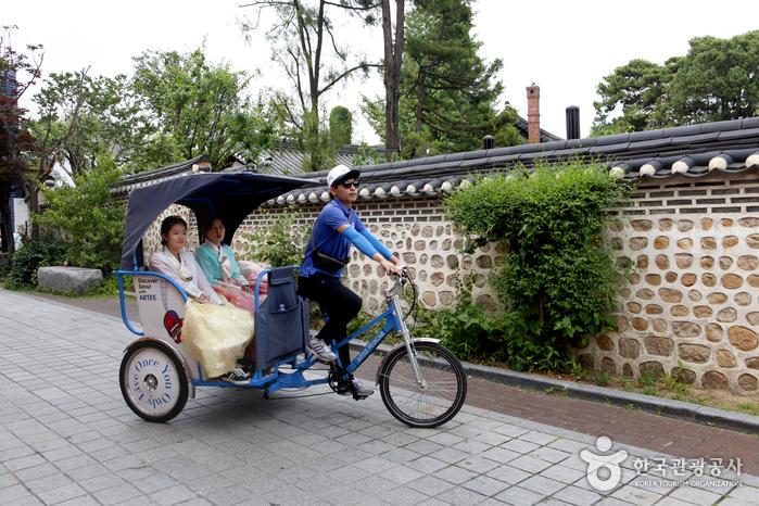 Two ladies in a Hanbok riding a rickshaw at Hanok Village.